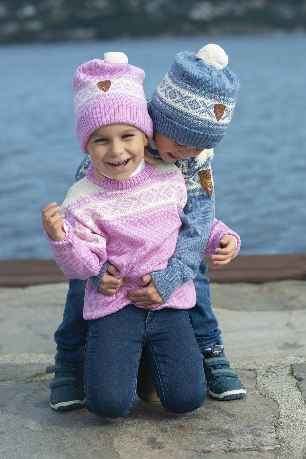 Children showing two colors of the Dale of Norway Cortina kids sweater. The colors are Pink Candy/Off White, 92991-I, and Blue Shadow/Off White, 92991-D