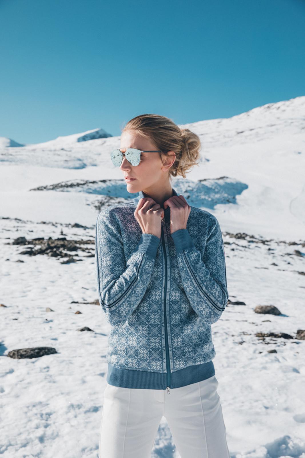 Woman standing in snow wearing Dale of Norway's Frida ladies cardigan in Blue Shadow/Off White/Grau Vig/Atlantic Mele, 82931-D