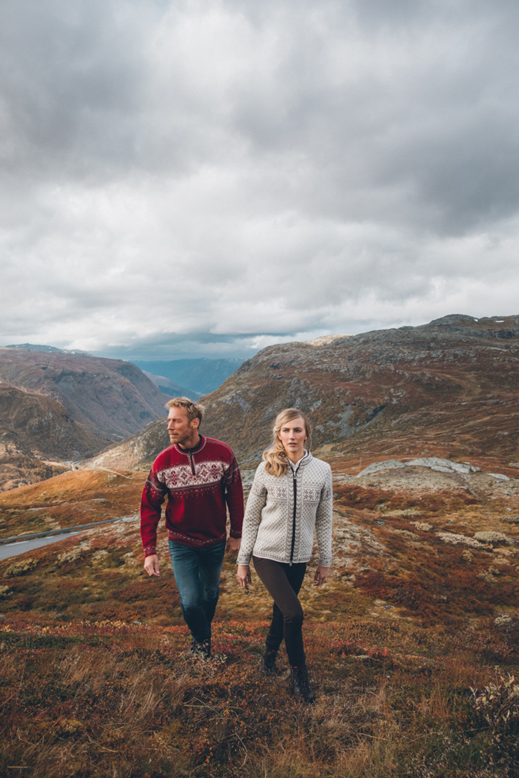Woman and man walking through field wearing the Dale of Norway Sunniva ladies cardigan in Off White/Warm Taupe, 83161-D, and the Blyfjell mens sweater in Red/Rose/Off-White/Mountainstone/Smoke, 91291-B, respectively