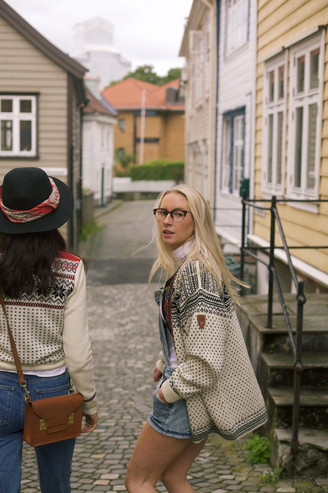 Women walking through Norwegian village wearing Dale of Norway Garmisch ladies sweater in Off White/Navy/Raspberry, 92601-A, and new unisex Setesdal cardigan in Off White/Black, 83291-A.