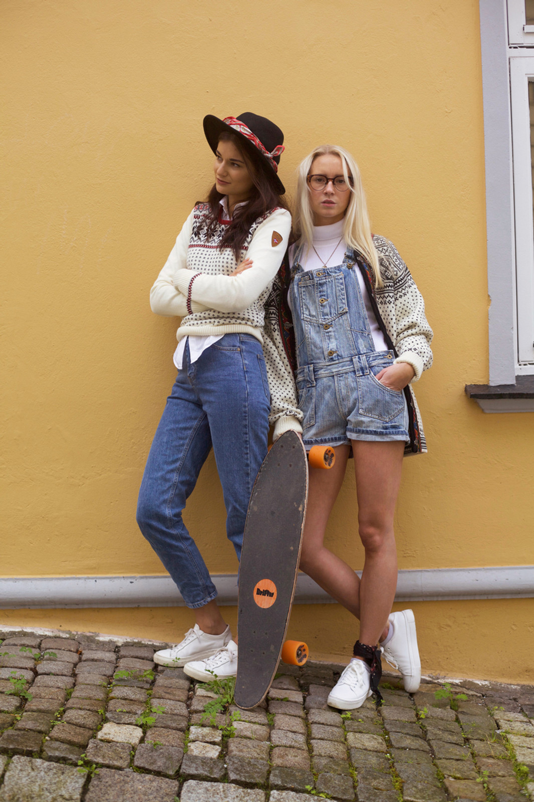 Women standing against wall wearing Dale of Norway Garmisch ladies sweater in Off White/Navy/Raspberry, 92601-A, and new unisex Setesdal cardigan in Off White/Black, 83291-A.