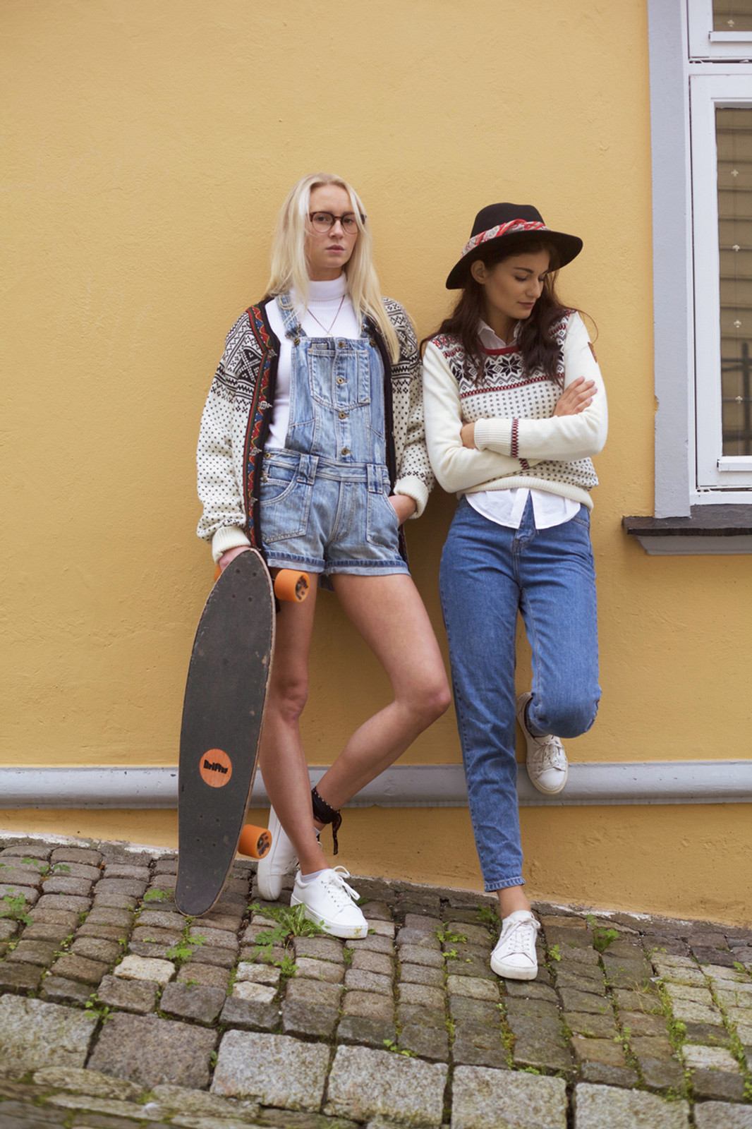 Woman with skateboard wearing Dale of Norway new unisex Setesdal cardigan in Off White/Black, 83291-A, standing against wall with woman wearing Dale of Norway Garmisch ladies sweater in Off White/Navy/Raspberry, 92601-A.