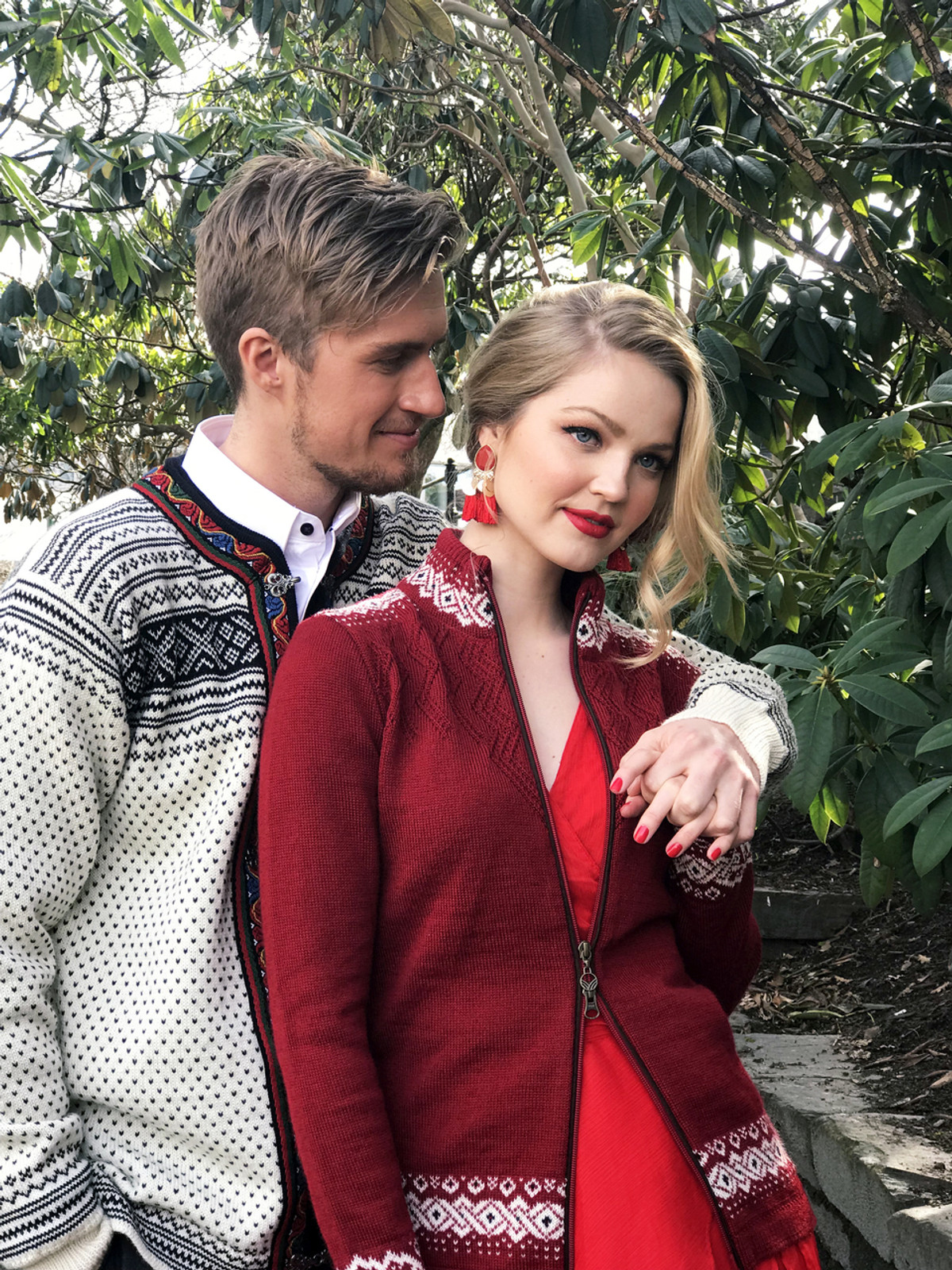 Man and woman in forest wearing Dale of Norway new unisex Setesdal cardigan in Off White/Black, 83291-A, and Bergen ladies cardigan in Red Rose/Off White/Navy, 83181-B
