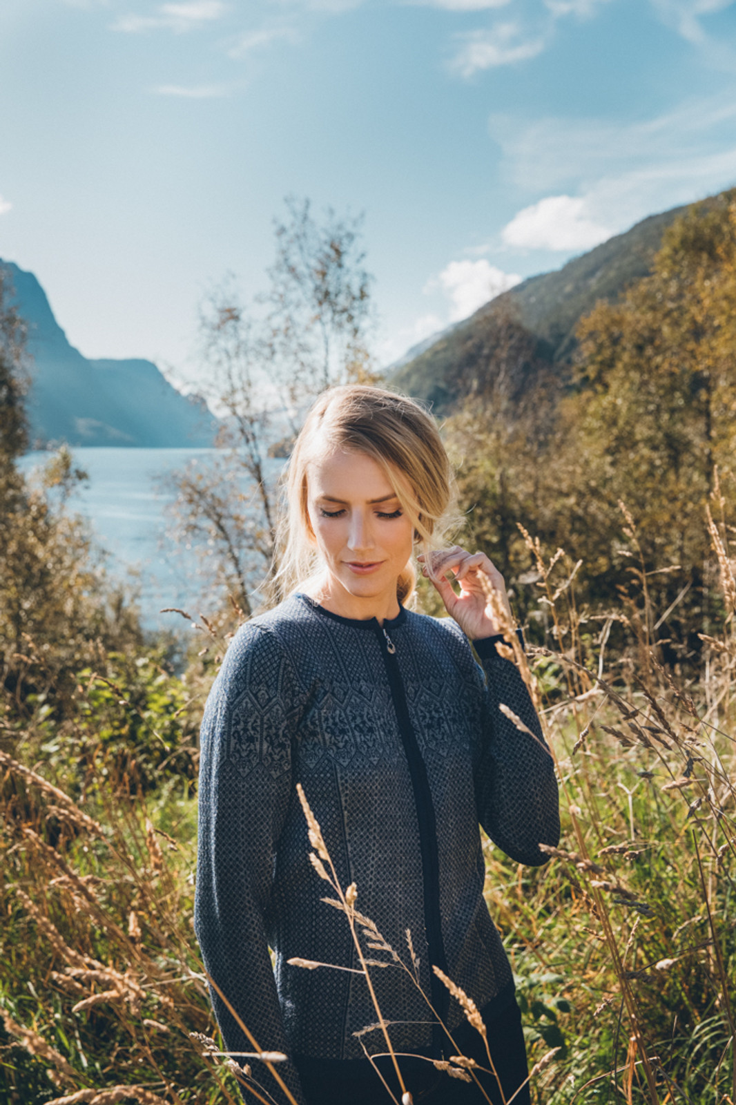 Woman standing in tall grass wearing Dale of Norway's Sigrid Ladies Cardigan in Electric Storm/Smoke, 82071-C