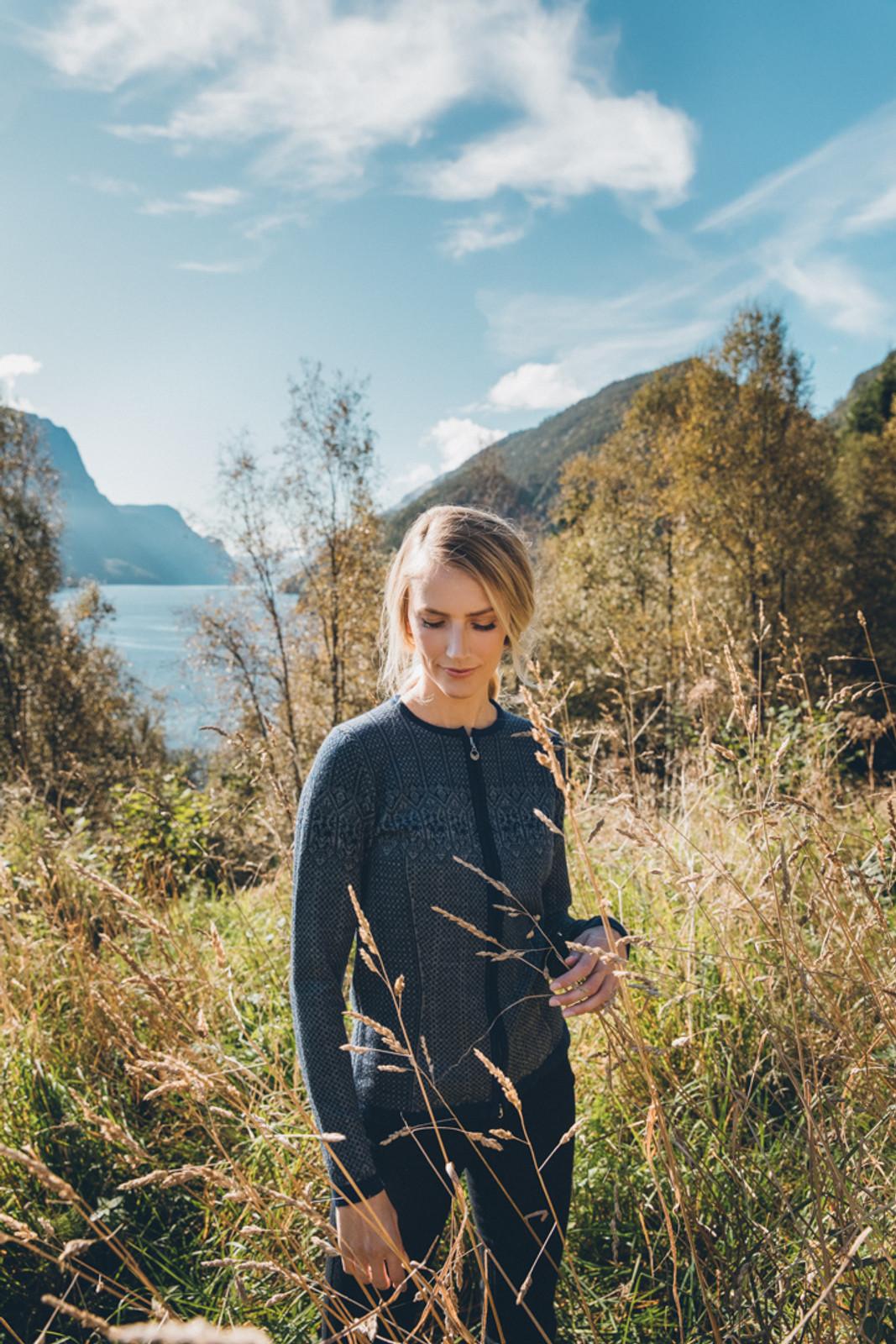 Woman walking through field wearing Dale of Norway's Sigrid Ladies Cardigan in Electric Storm/Smoke, 82071-C
