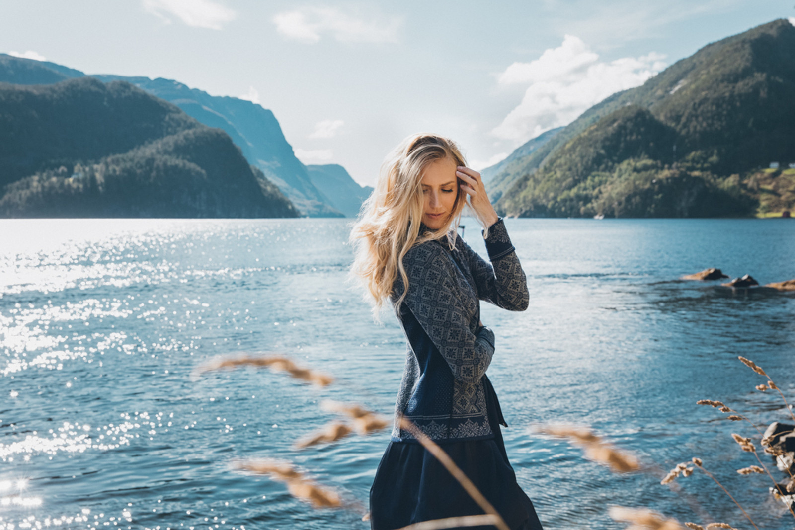 Woman by lakeshore wearing Dale of Norway's Christiania Ladies Cardigan in Electric Storm/Smoke, 81951-H