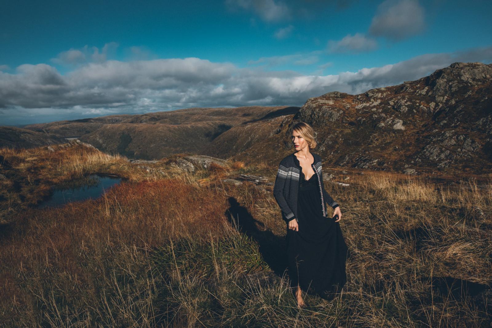 Woman in field wearing Dale of Norway's Hedda Ladies Cardigan in Black/Off White/Ruby Mel, 83401-F