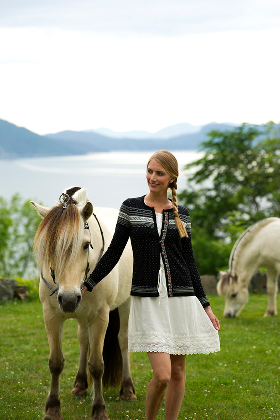 Woman with horse wearing Dale of Norway's Hedda Ladies Cardigan in Black/Off White/Ruby Mel, 83401-F