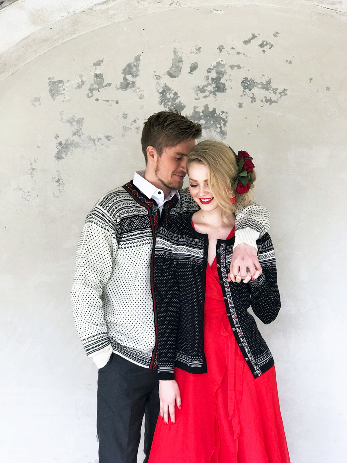 Man and woman wearing Dale of Norway new unisex Setesdal cardigan in Off White/Black, 83291-A, and Hedda Ladies Cardigan in Black/Off White/Ruby Mel, 83401-F