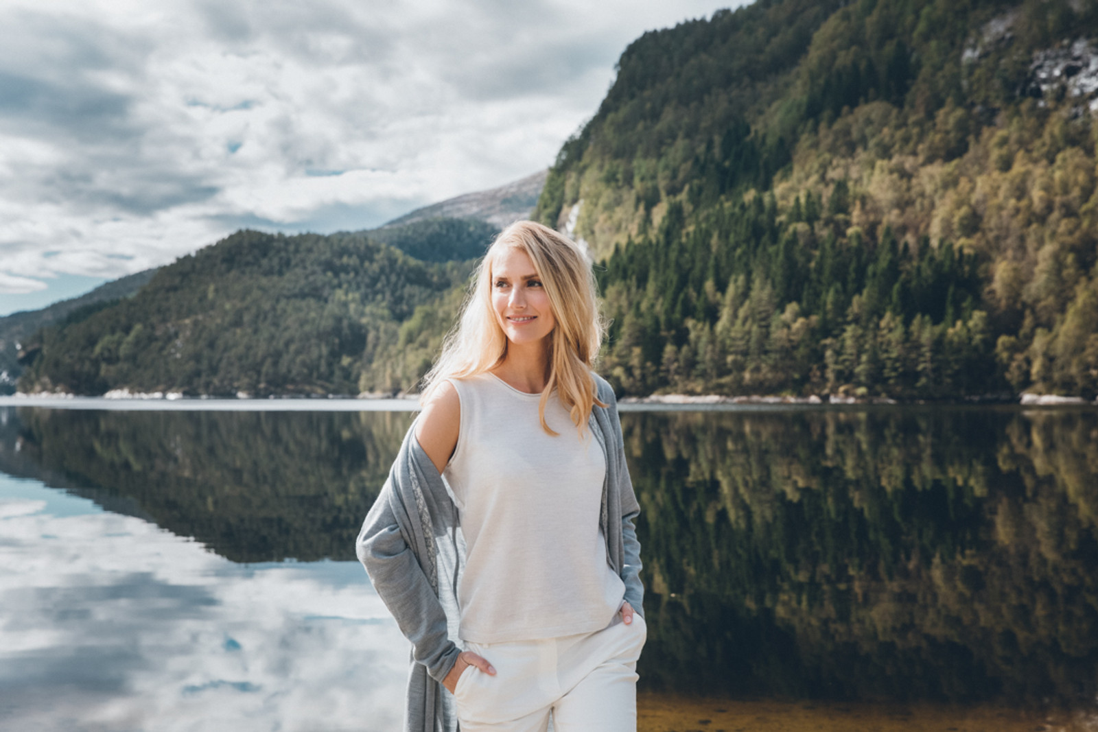 Woman standing by lakeshore wearing Dale of Norway's Stjerne Ladies Top in Off White Mel, 93701-A, under a Nora ladies jacket in Grau Vig/Off White, 83331-T