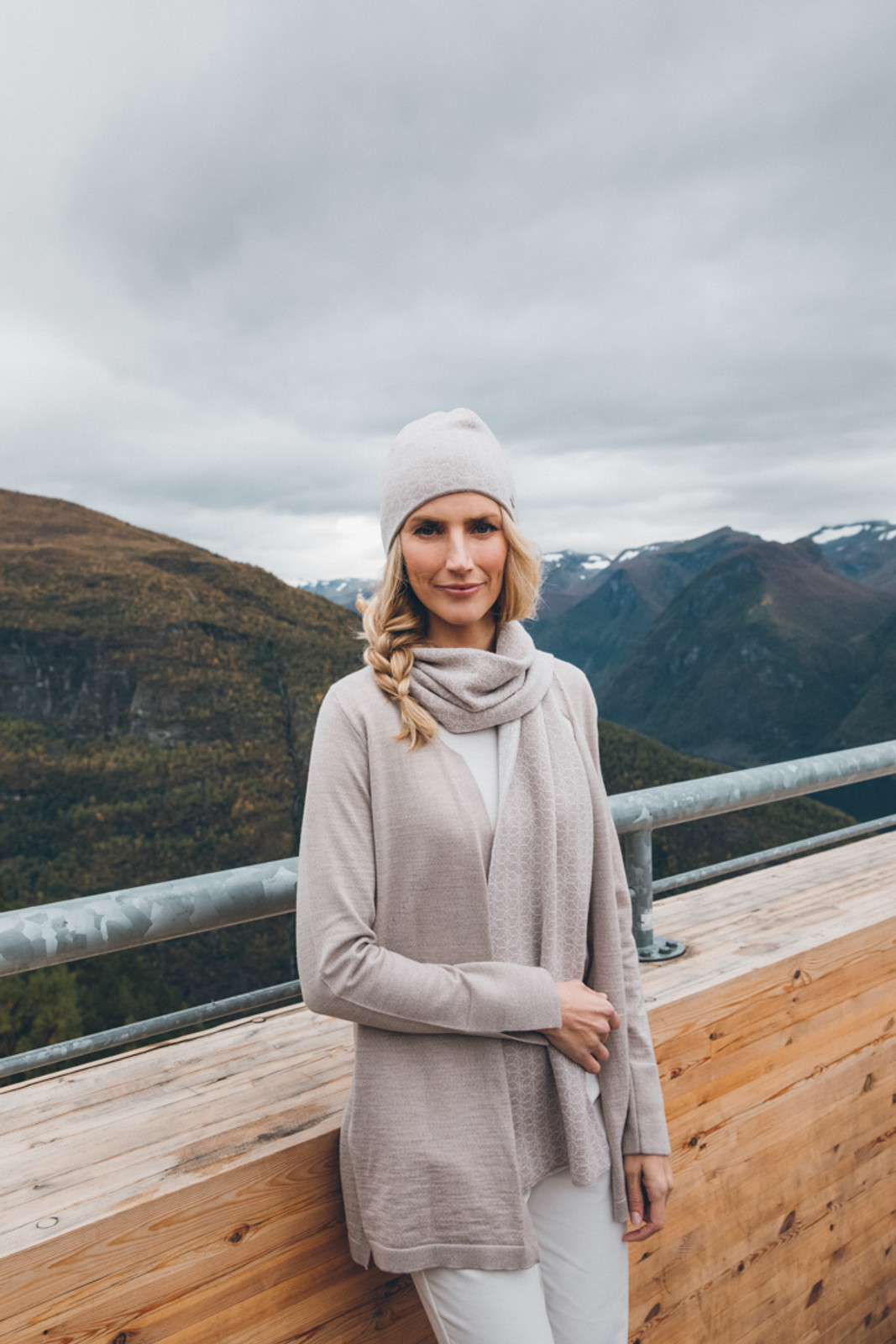 Woman wearing Dale of Norway's Marie ladies cardigan in Sand, 83351-P, with Stjerne hat in Sand Mel/Off White Mel, 48121-P, and Stjerne Scarf in Sand Mel/Off White Mel 11671-P.