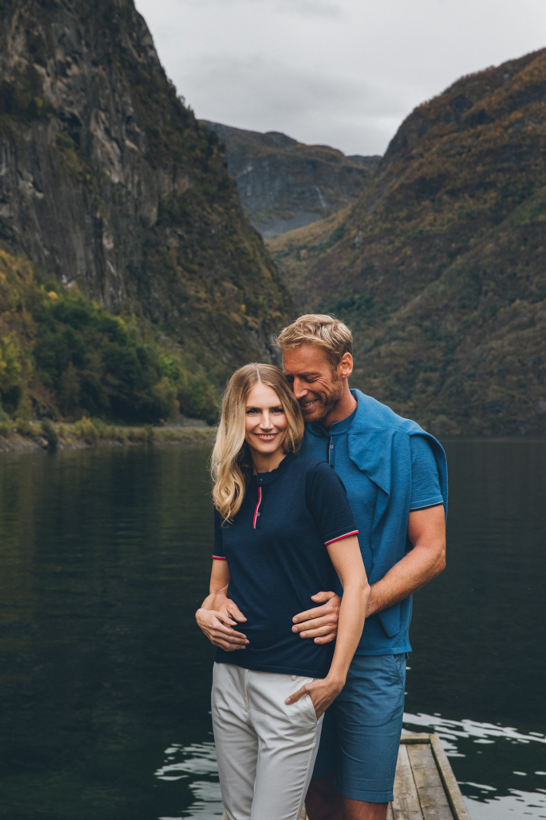 Couple standing on dock wearing Dale of Norway's Fredrikke ladies T-shirt in Navy/Red Rose/Off White, 93841-C and Fredrik mens T-shirt in Medium Blue Mel/Light Grey/Off White Mel/Navy Mel, 93771-H