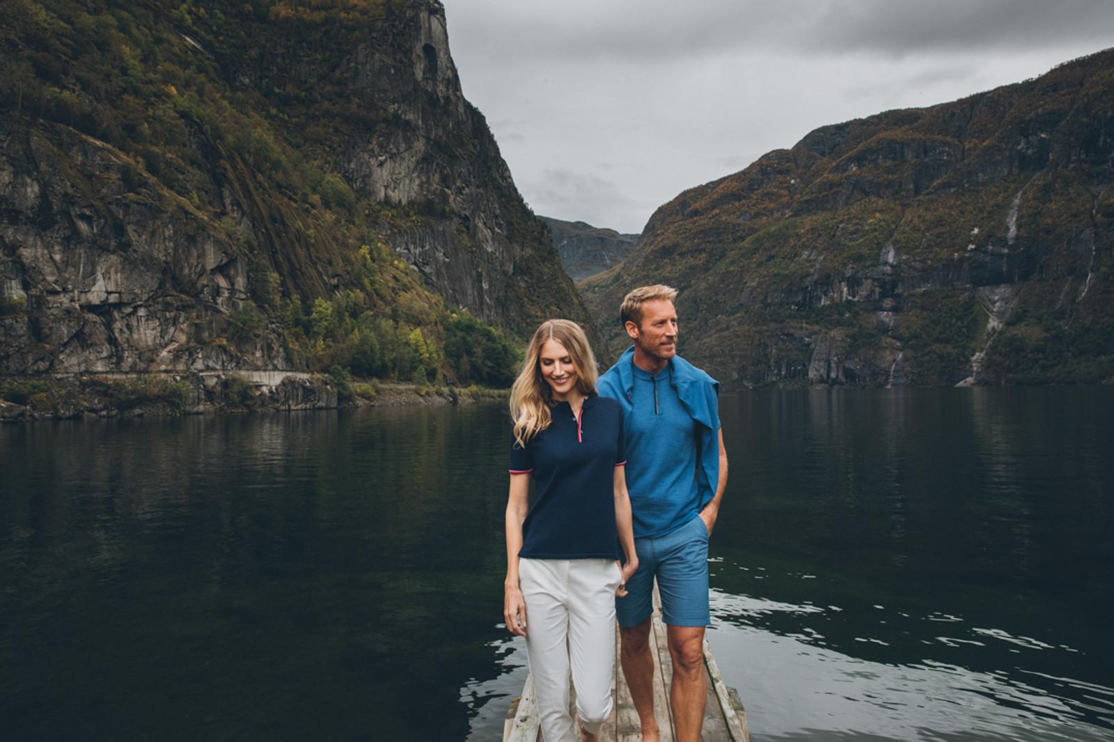 Couple walking on dock wearing Dale of Norway's Fredrikke ladies T-shirt in Navy/Red Rose/Off White, 93841-C and Fredrik mens T-shirt in Medium Blue Mel/Light Grey/Off White Mel/Navy Mel, 93771-H