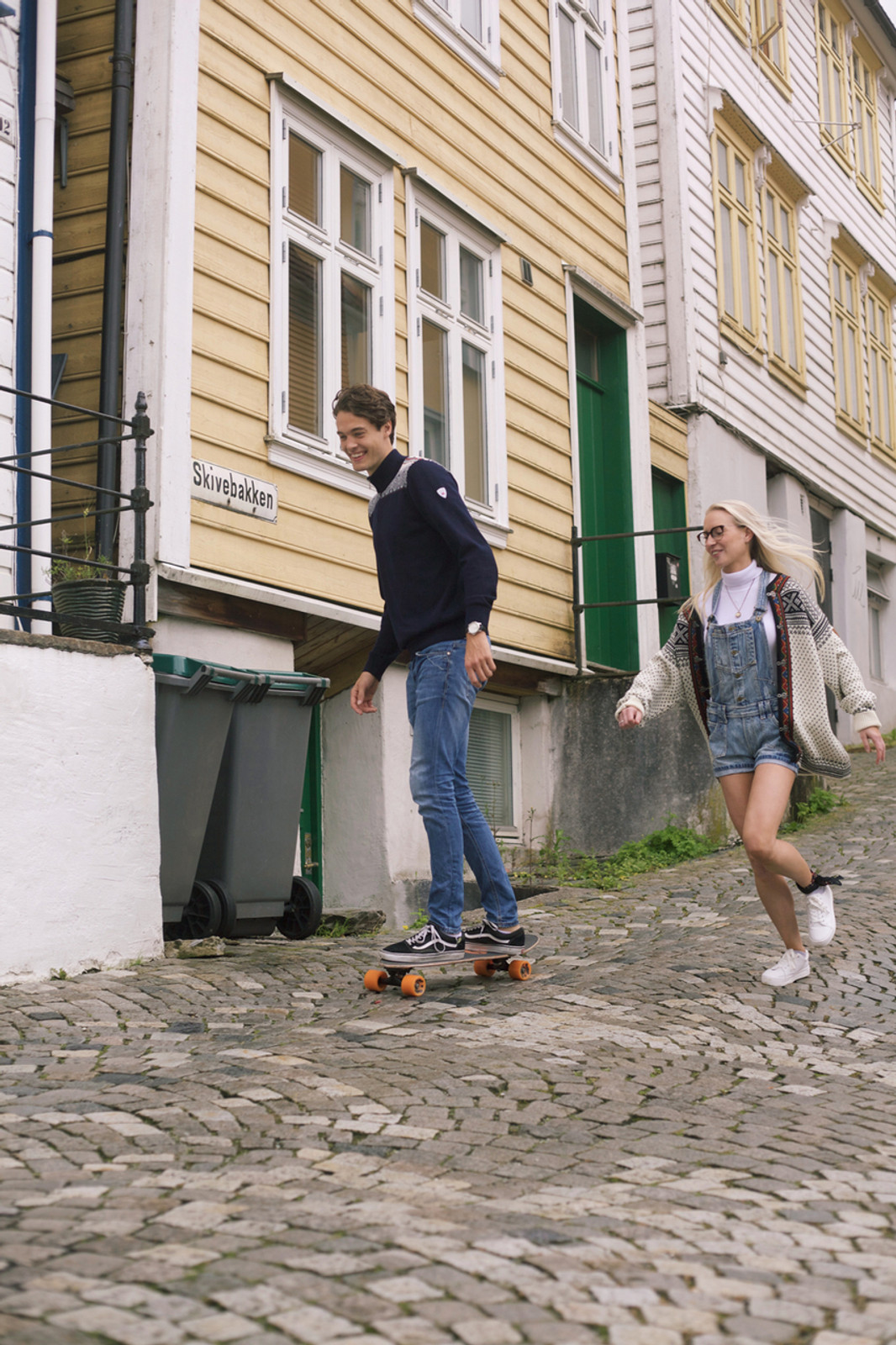 Skating boy and running girl wearing Dale of Norway mens Fiemme Sweater in Dark Charcoal/Grau Vig/Raspberry/Off White, 93421-T, and new unisex Setesdal cardigan in Off White/Black, 83291-A