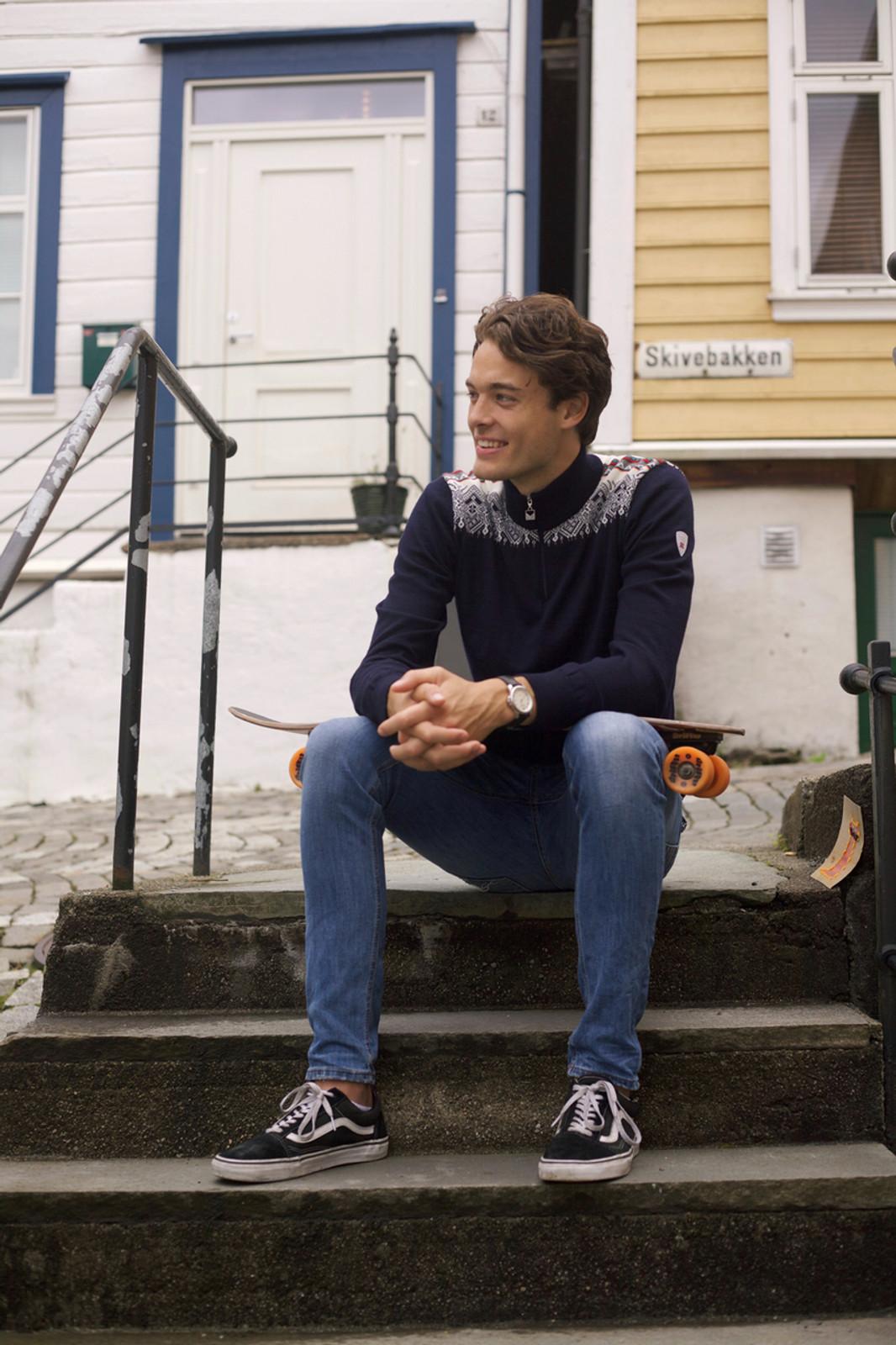Boy sitting wearing Dale of Norway mens Fiemme Sweater in Dark Charcoal/Grau Vig/Raspberry/Off White, 93421-T.