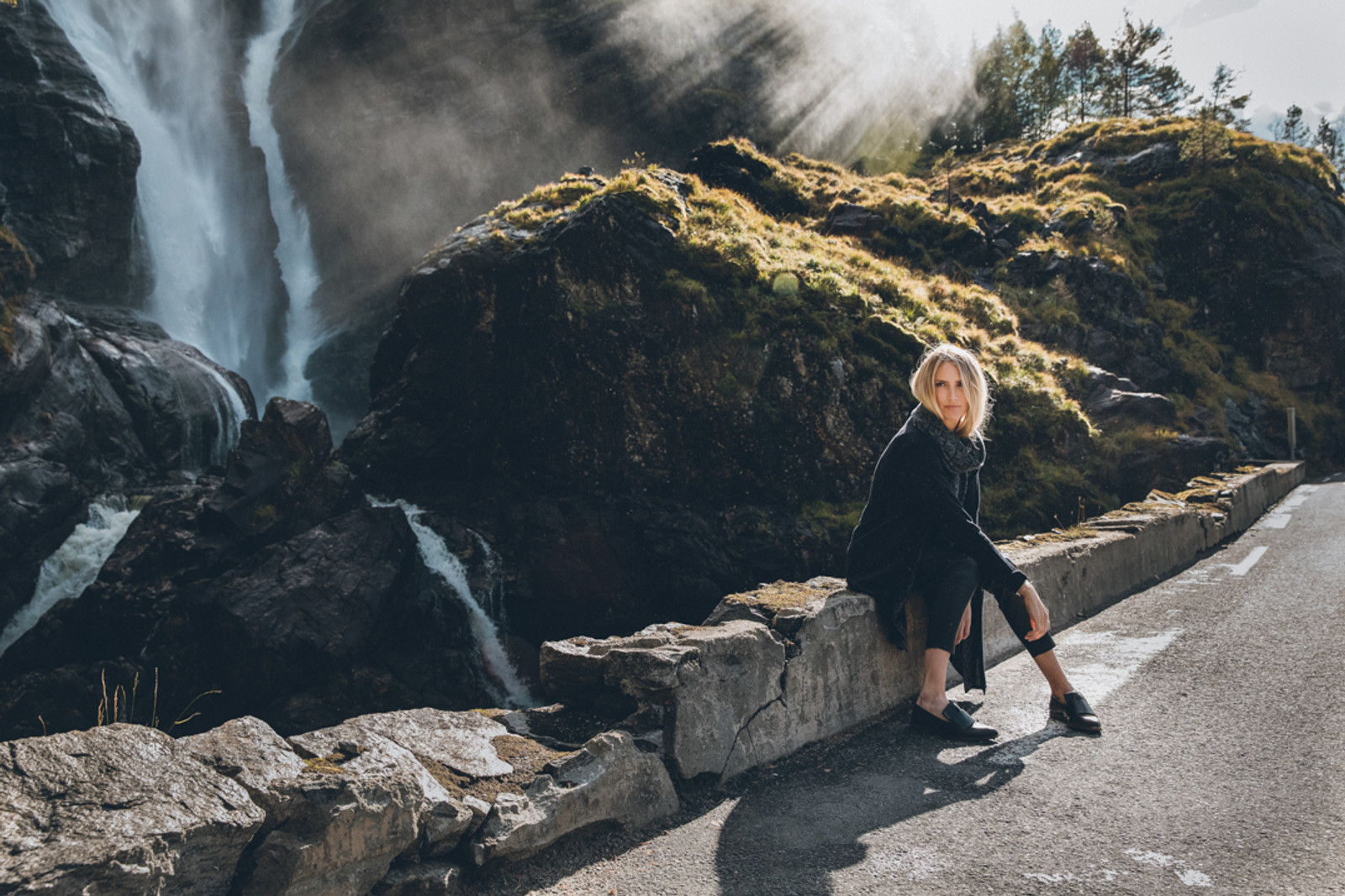 Woman sitting by side of the road wearing Dale of Norway's Nora Ladies Jacket in Black/Smoke, 83331-F, and Flora Scarf in Black/Dark Grey Mel, 11681-F