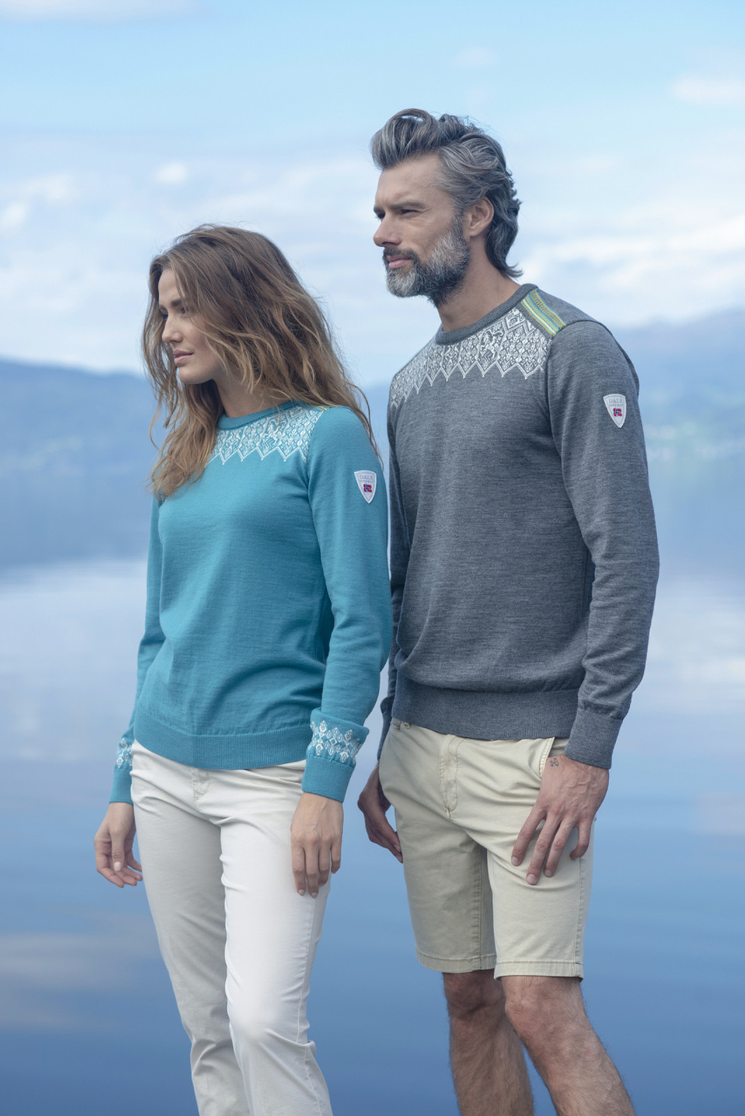 Woman wearing Ladies Dale of Norway Lillehammer Sweater in Turquoise, 93261-G and Man wearing Mens Dale of Norway Lillehammer Sweater in Smoke 93271-E