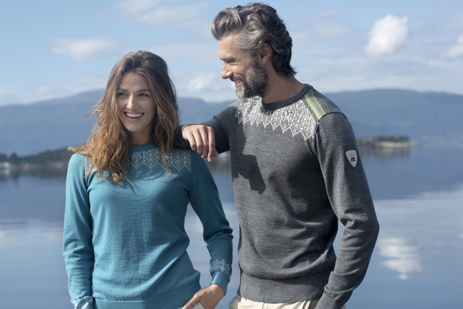 Woman wearing Dale of Norway Women's Lillehammer Sweater in Turquoise, 93261-G and man wearing Dale of Norway Men's Lillehammer Sweater in Smoke/Off White/Arctic Blue/Turquoise, 93271-E
