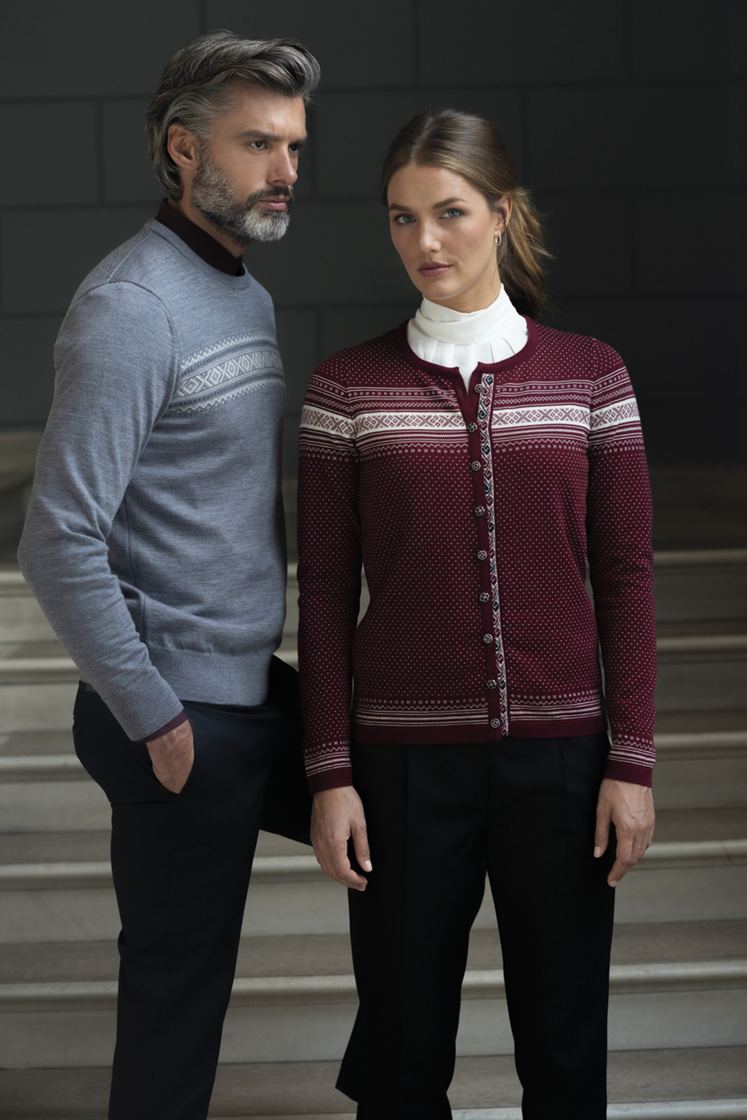 Man wearing Dale of Norway Sverre Sweater in Smoke/Off White/Dark Charcoal, 93031-T and woman wearing Dale of Norway Hedda Cardigan, Ladies in Ruby Melange/Off White/Dark Charcoal, 83401-V
