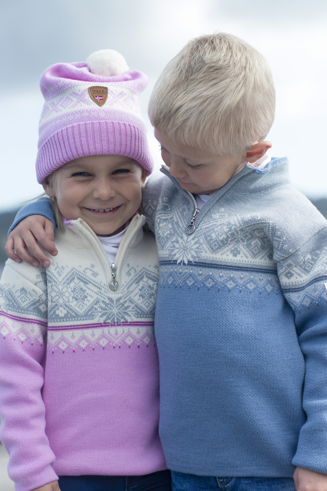 Children wearing Dale of Norway Moritz Sweaters in Pink Candy and Blue Shadow, 9150-Q and 9150-D