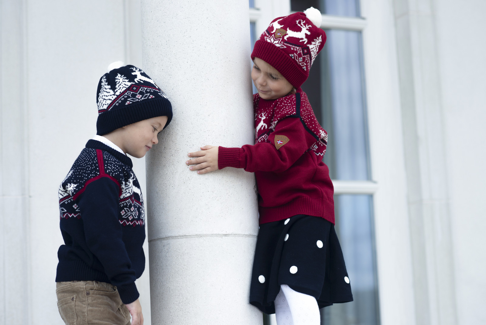 Kids playing wearing Dale of Norway Dale Christmas sweaters in Navy, 93941-C, and Red Rose, 93941-B