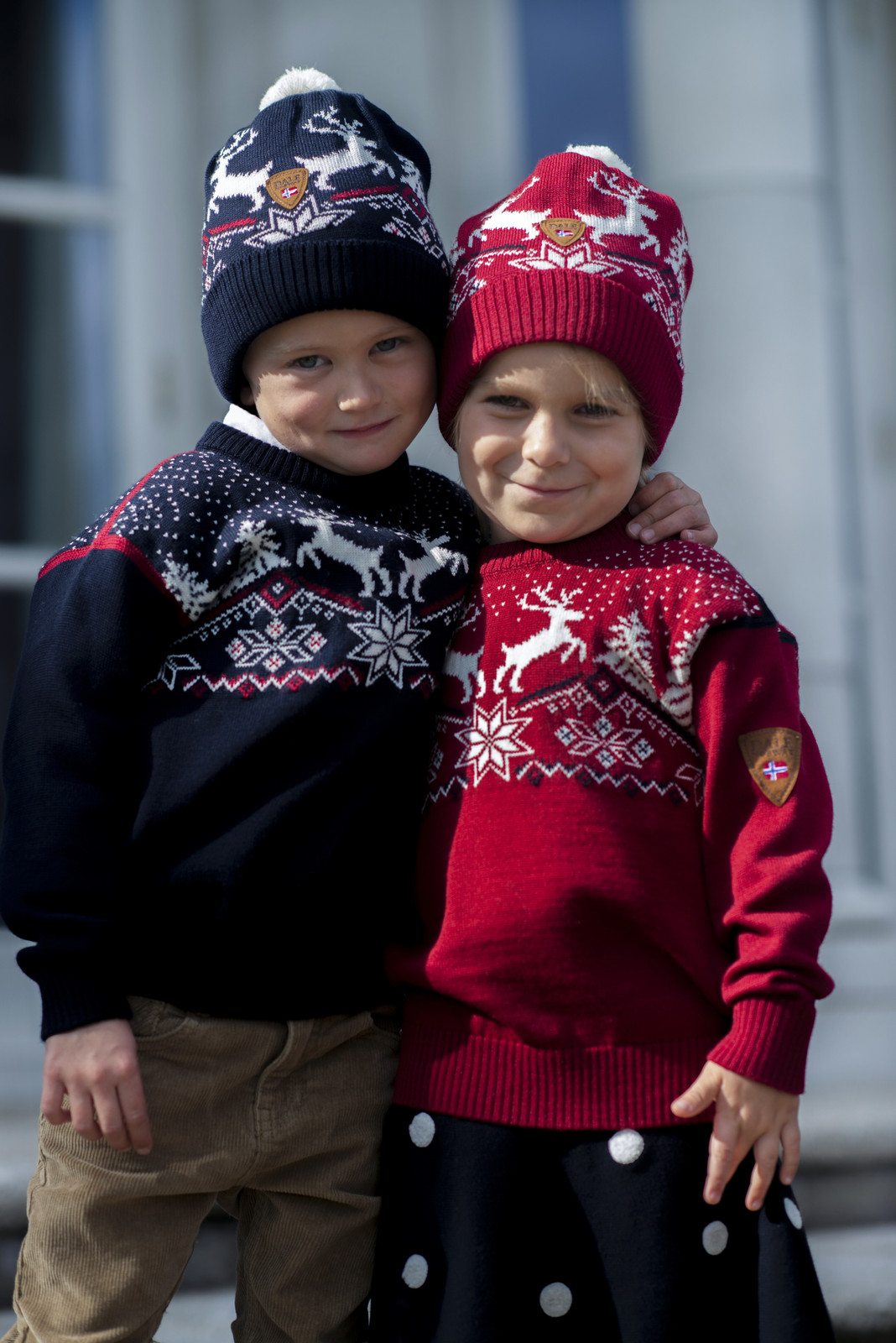 Kids wearing Dale of Norway Dale Christmas sweaters in Navy, 93941-C, and Red Rose, 93941-B