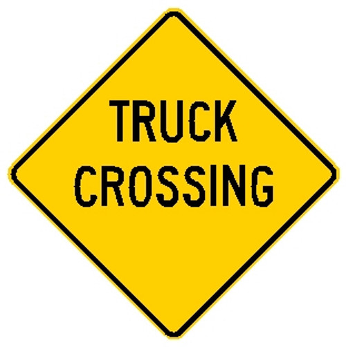 """Yellow sign, says """"Truck Crossing"""" in black letters"""