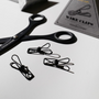 Three Tools to Liveby Wire Clips photographed with scissors and a box