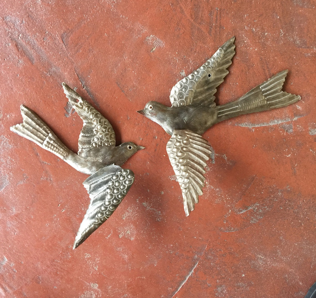 Haiti metal birds with 3-d wings hung on stucco wall