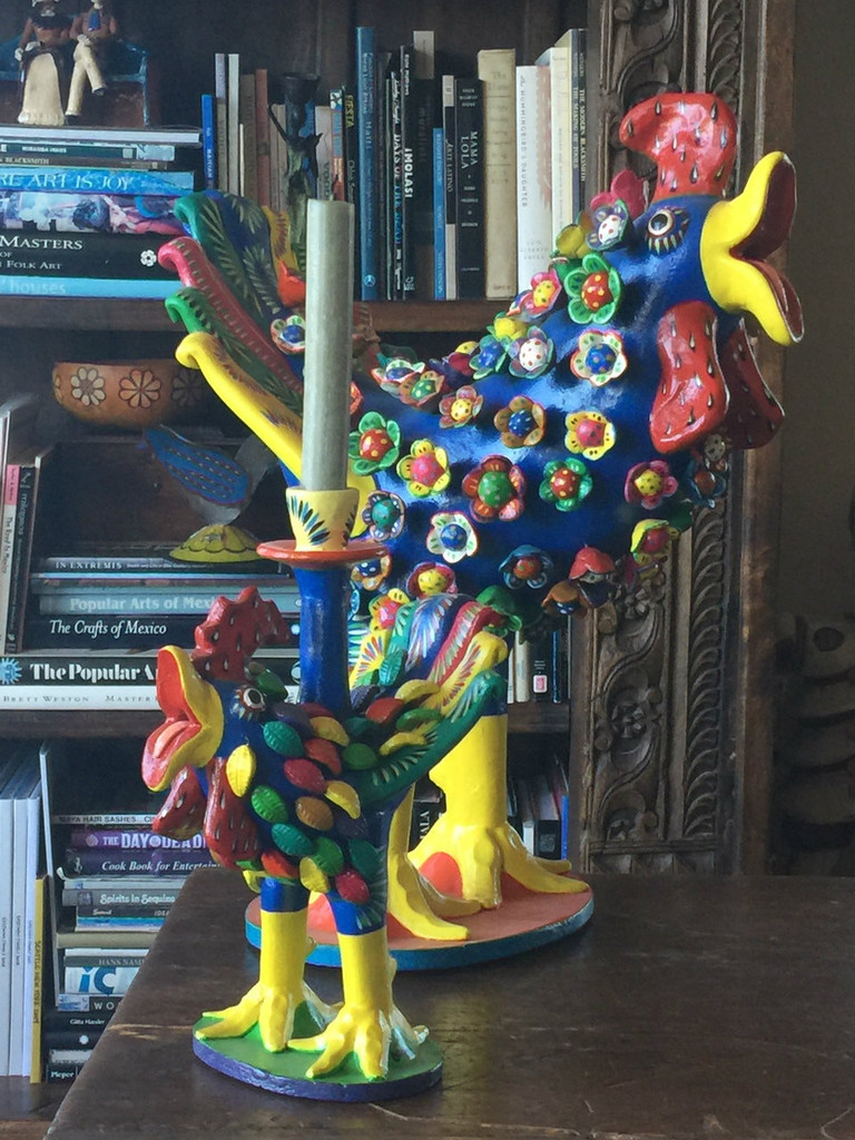 The rooster is blue, standing upright on an orange base.  His body is covered with bright colorful miniature flower designs,  and an orange tongue pokes through an open yellow beak.  The tail feathers are truly unique on this piece and feature a symmetrical design of red and yellow with light and dark blues.