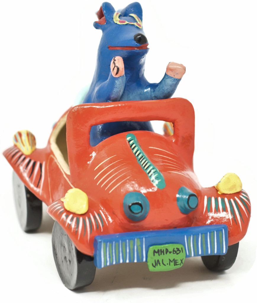 Authentic Mexican folk art by artist Gerardo Ortega of Jalisco.  This is a happy dog driving a fancy orange car in the Barro Betus technique.