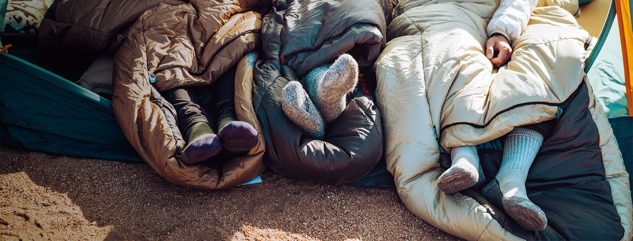 Campers with feet sticking out of sleeping bags