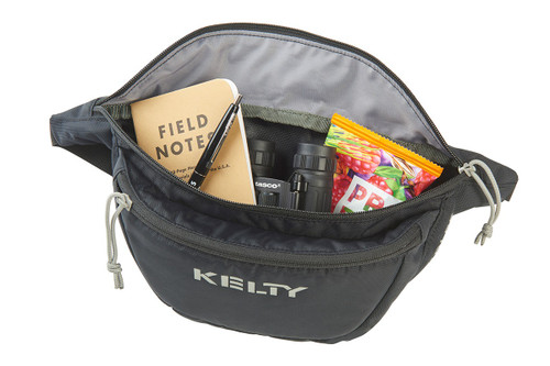 Kelty Warbler waist pack, black, unzipped to show notebook, snacks, and other items stored inside