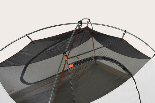 Close up of the top of Kelty Outfitter Pro 2 person tent, showing grey mesh at the top of the tent body, and two tent poles attached with color-coded plastic clips