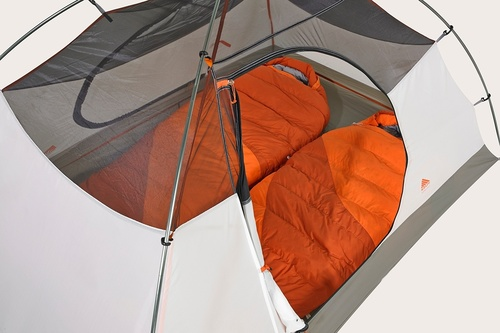 Close up of the Kelty Outfitter Pro 2 person tent, showing front door unzipped, rolled up, and secured with a toggle to the tent body