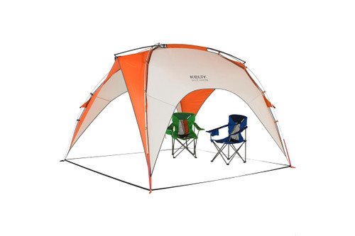Kelty Shade Maker 2 sun shelter, orange/white, front view, with two folding chairs underneath