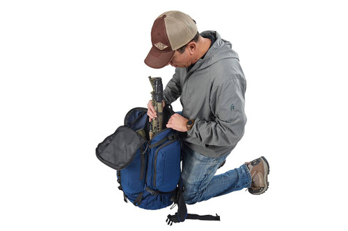 Man kneeling beside Kelty Redwing 50 USA backpack, putting gear inside the pack