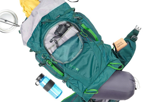 Kelty Coyote 80 backpack, Ponderosa Pine, shown overhead with an assortment of camping gear, including a sleeping bag, water bottle, rain jacket, headlamp, and binoculars
