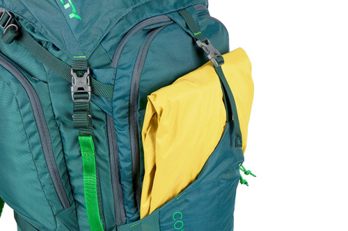 Close up of Kelty Coyote 80 backpack, Ponderosa Pine, showing a yellow rain jacket inside exterior storage compartment