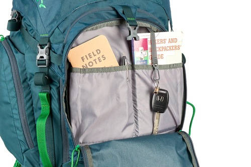 Close up of Kelty Coyote 80 backpack, Ponderosa Pine, with front compartment unzipped, showing multiple storage pockets