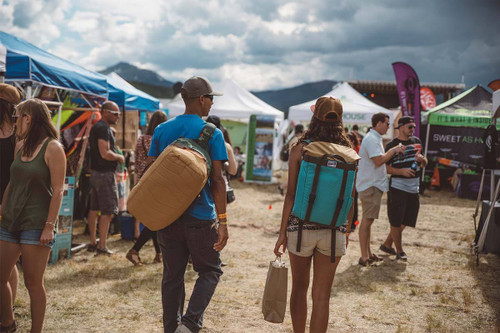 Man at a festival, carrying Kelty Dodger Duffel bag on his back