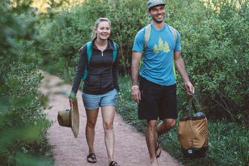 Happy couple walking down a gravel path, carrying a Kelty Totes Tote