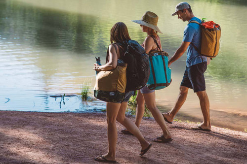 Three friends carrying Kelty Totes Totes next to a lake