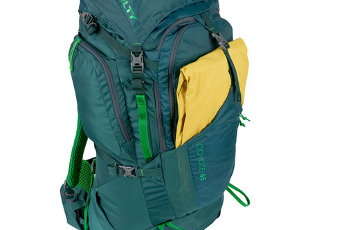 Close up of Kelty Coyote 65 backpack, Ponderosa Pine, showing a yellow rain jacket inside exterior storage compartment