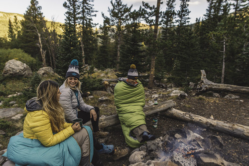Trio of campers wearing Kelty Tuck 20 Degree Sleeping Bags next to a campfire