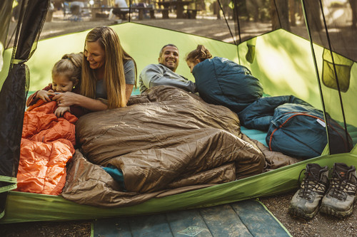 Family camping in tent, inside their sleeping bags