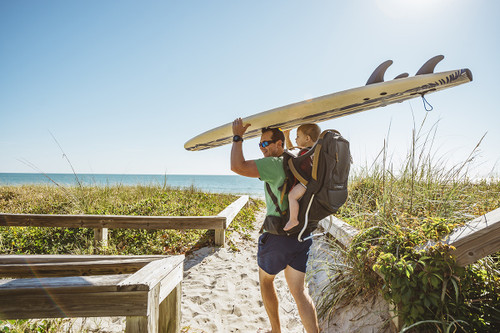 Father carrying child in Kelty Journey PerfectFIT Elite, while holding a surfboard over his head