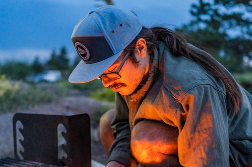 Hipster with nerdy glasses, bushy moustache, and ponytail wearing Kelty 7 Panel PITW Hat