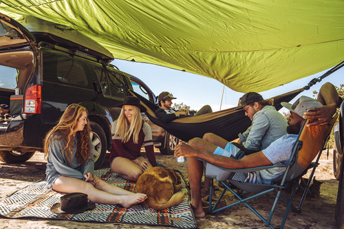 Group of friends under tarp, sitting on Kelty Bestie BFF Blanket with a super cute dog