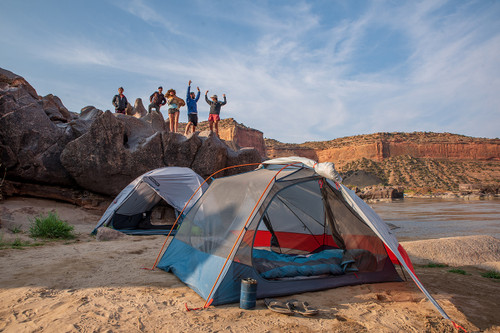 Group of friends standing behind two Kelty Dirt Motel 3 person tents in the desert